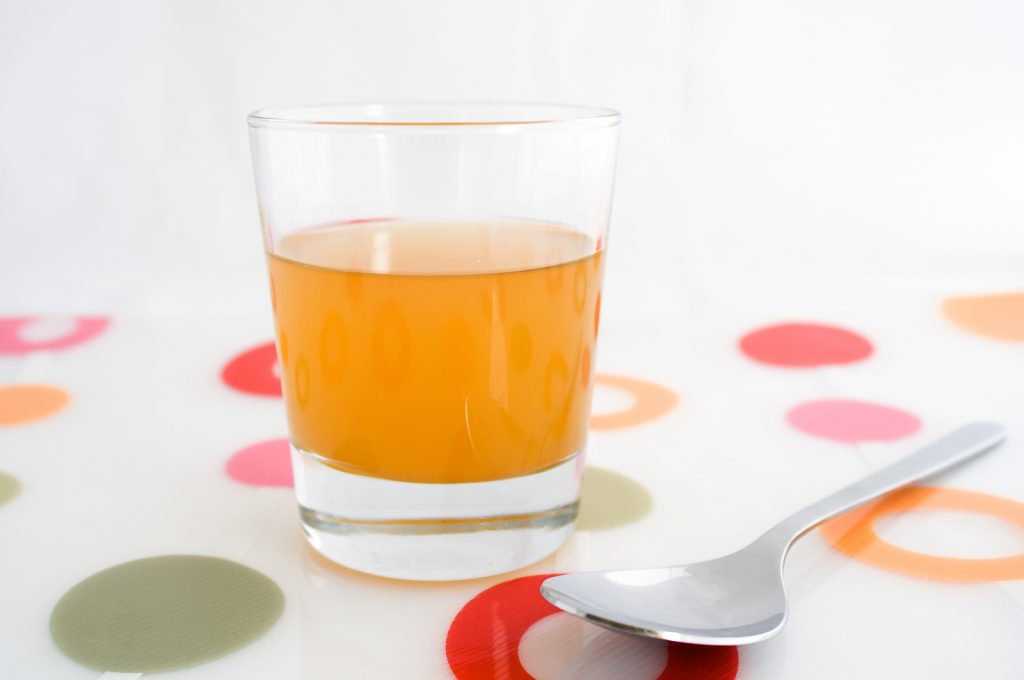 apple cider vinegar in glass and spoon